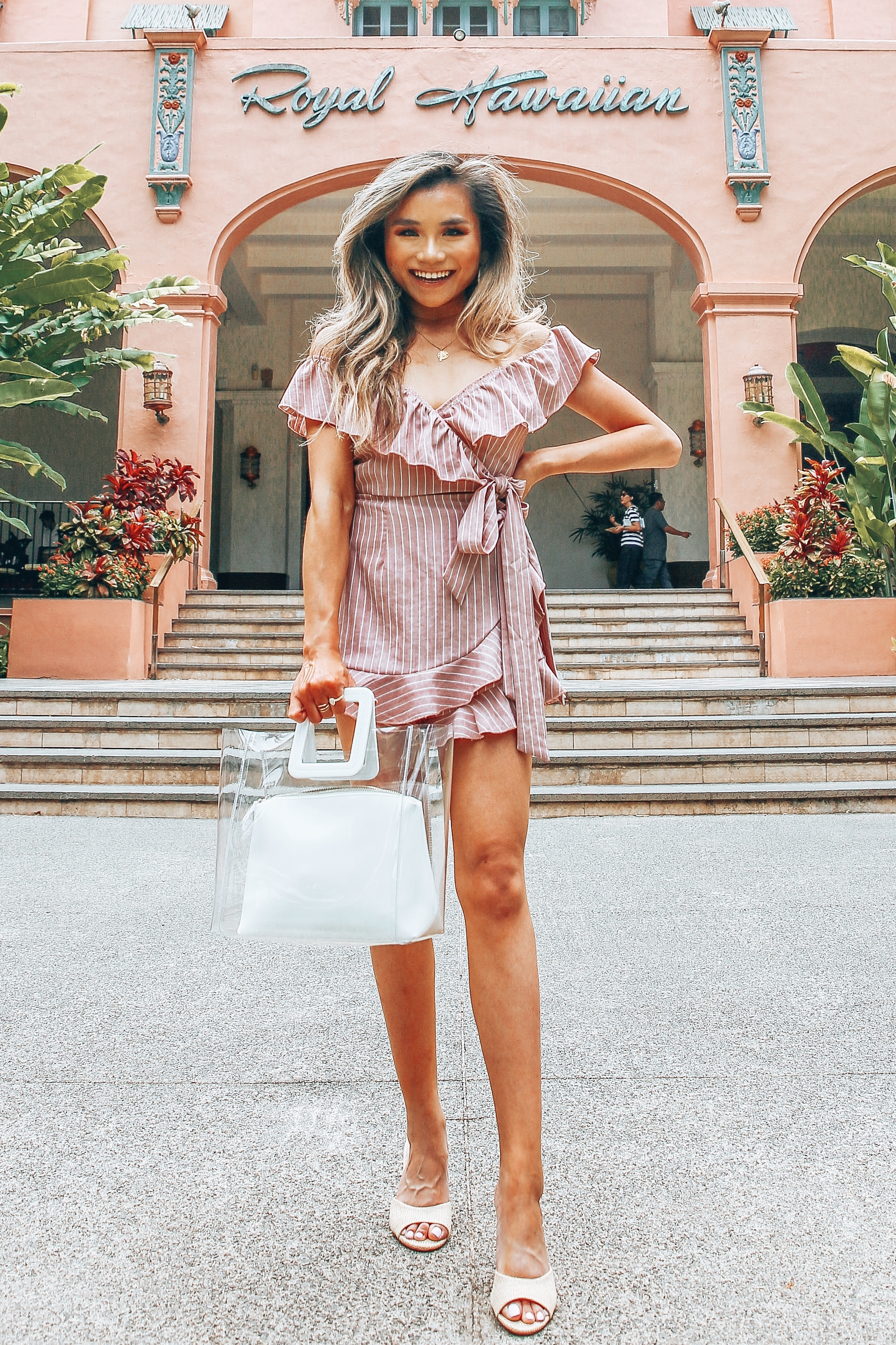 miss louie wearing summer vacation outfit with Revolve superdown ruffle romper, staud shirley tote, and steve madden erin sandals